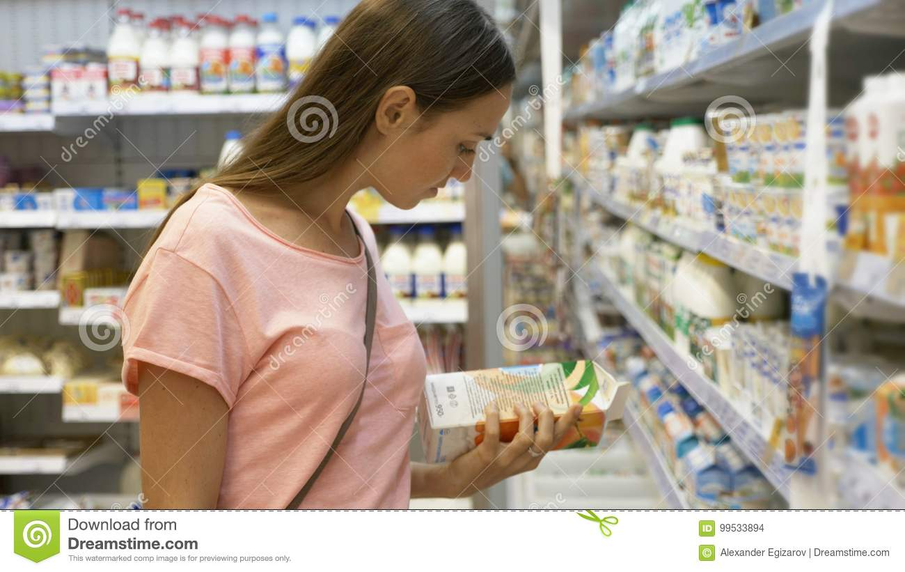 Woman selecting dairy food in fridge at grocery department of shopping mall