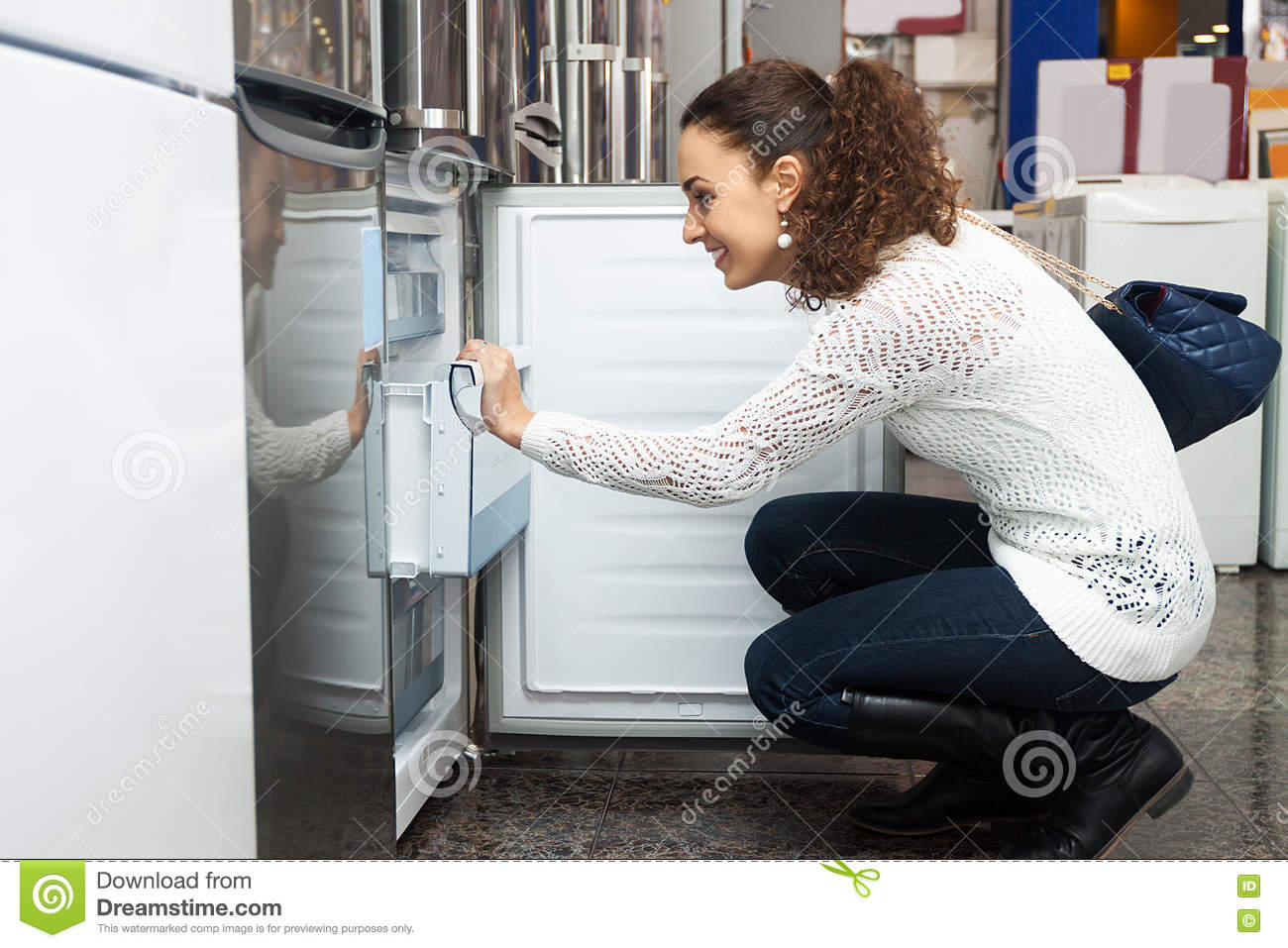 Young woman selecting domestic refrigerator