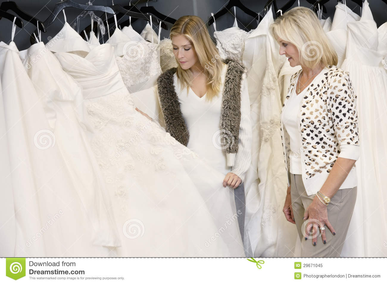 Young Woman With Senior Mother Selecting Wedding Dress In