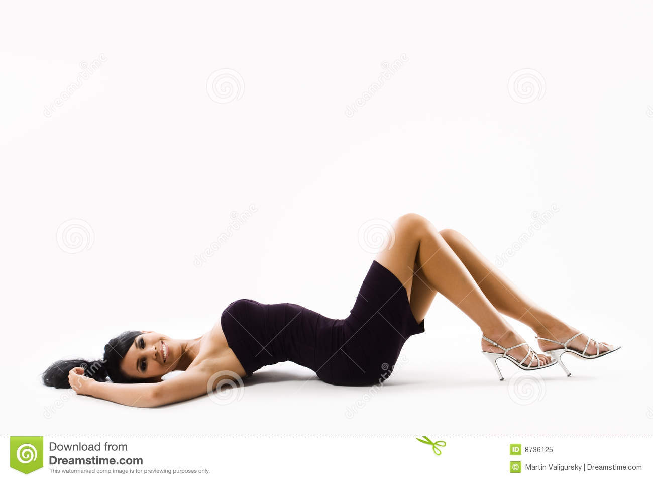 Young woman in dress lying on back