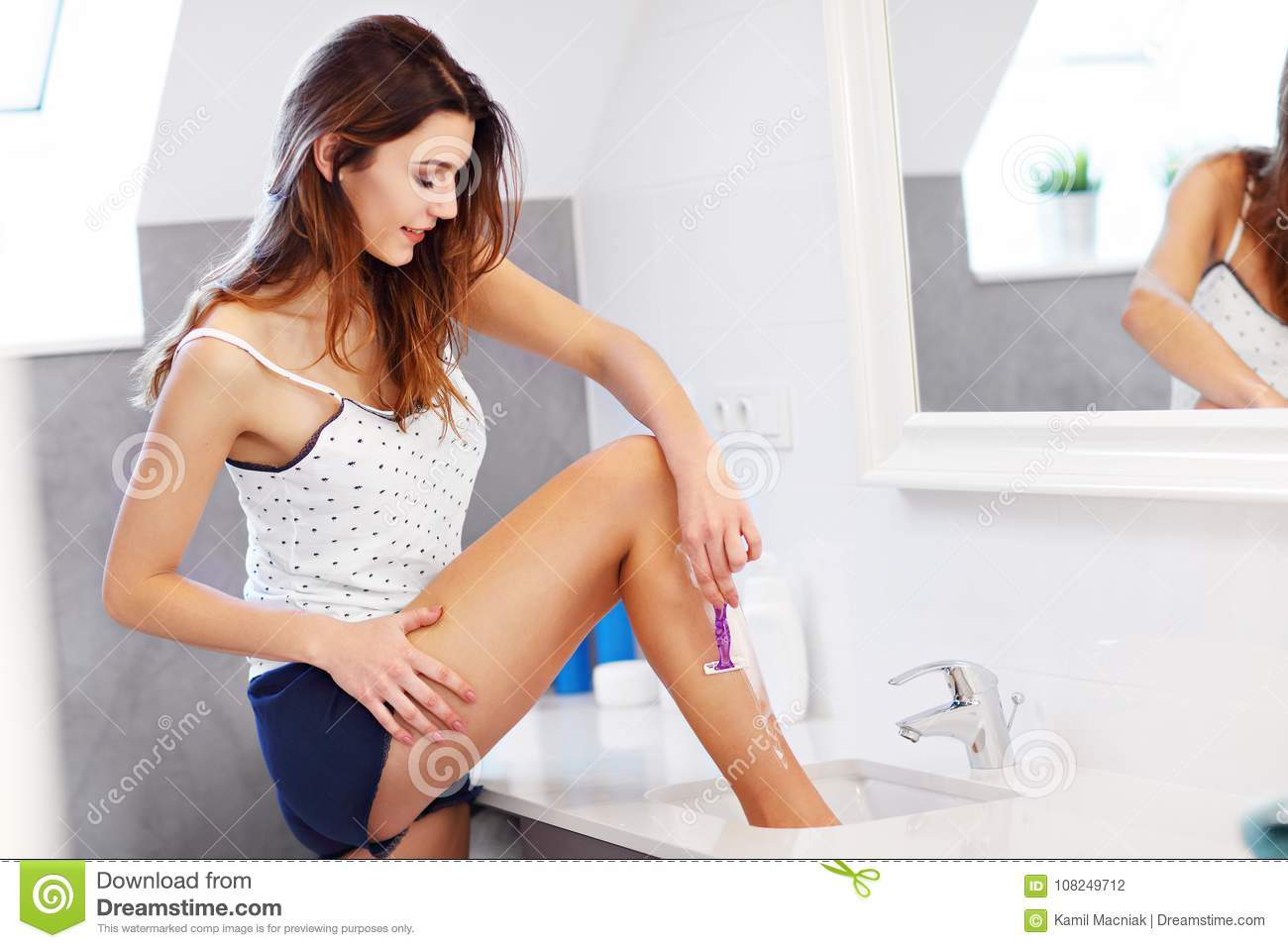 Young woman shaving legs in bathroom in the morning