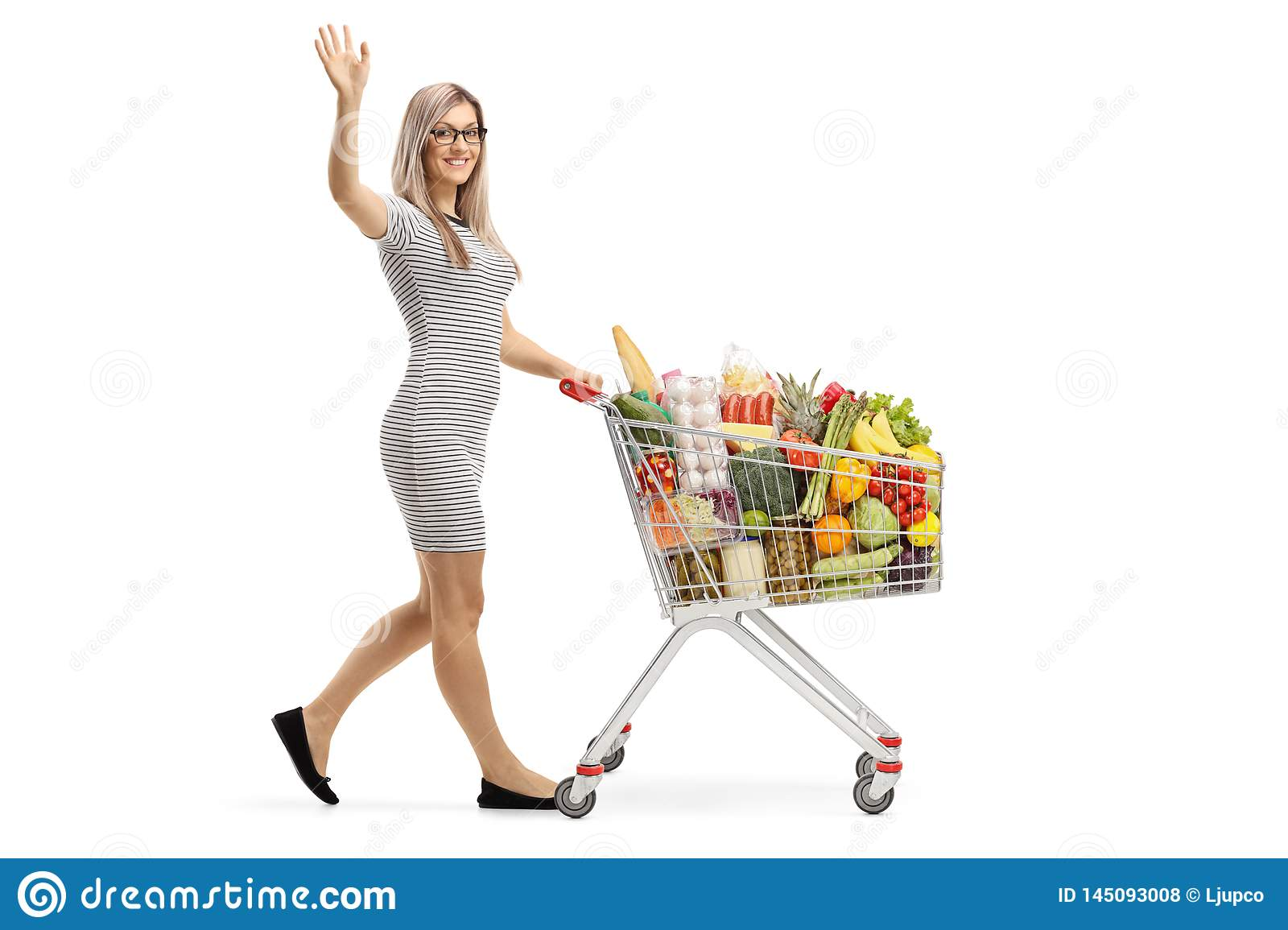 Young woman with a shopping cart full of food products waving