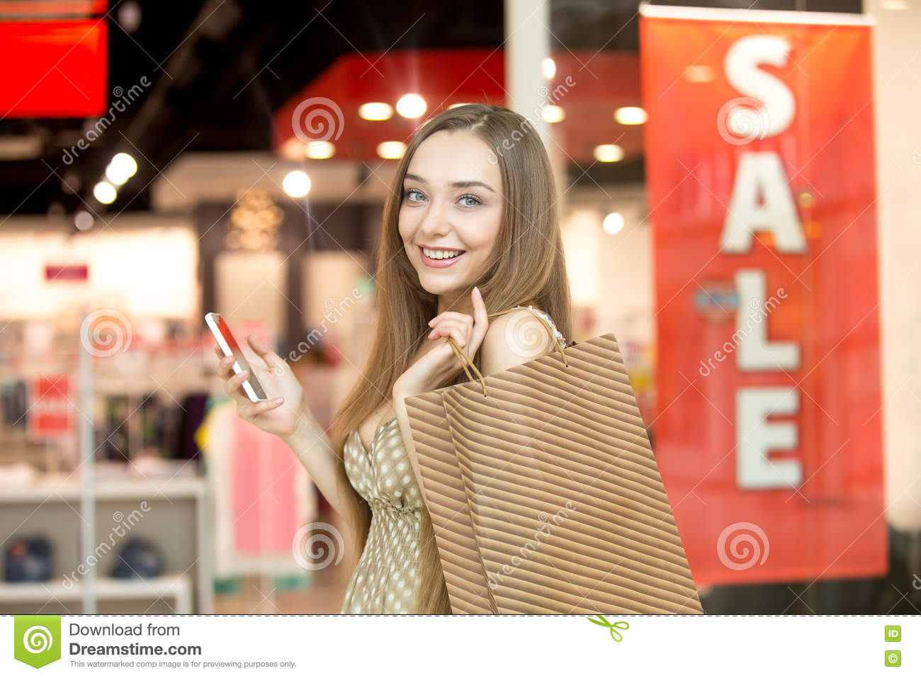 Young woman in a shopping centre holding a phone smiling