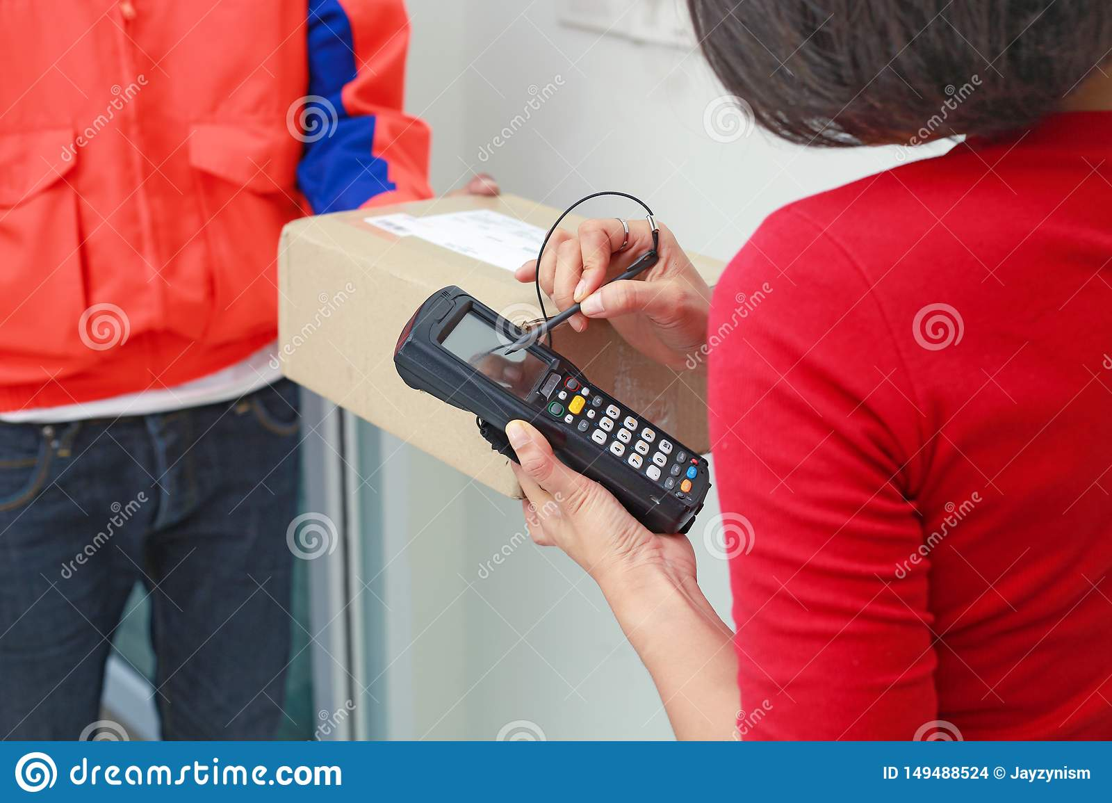Young woman sign in digital mobile phone after receiving parcel at home