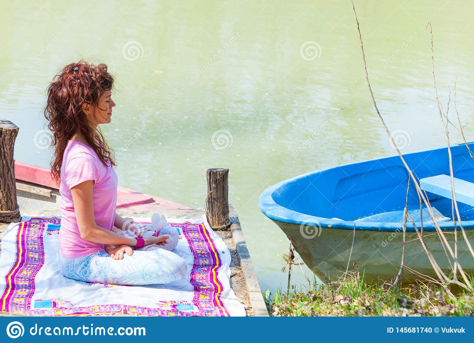 Young woman sit in a meditative yoga position on wooden pontoon on the lake hold magnolia flower