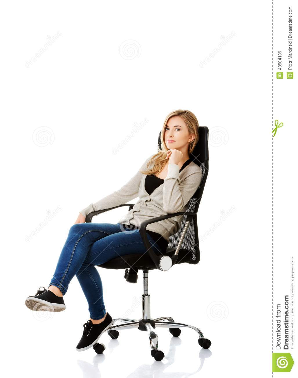 Young woman sitting on armchair touching chin stock photo for Sitting in armchair
