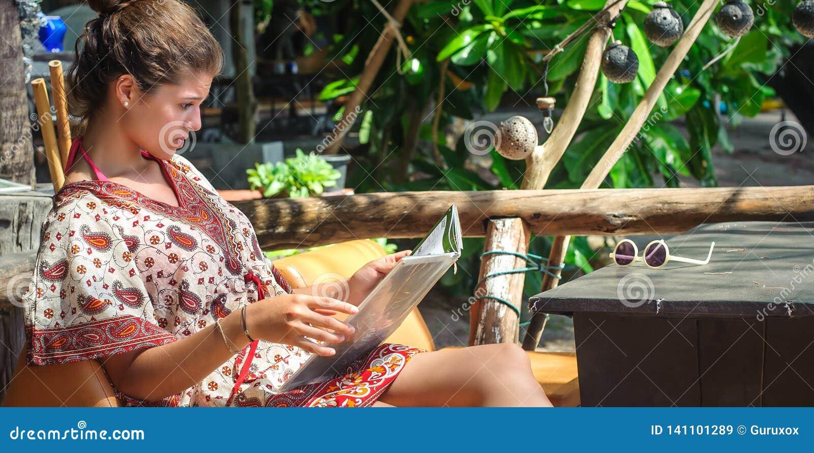 Young woman sitting in bamboo beach bar, looking at menu