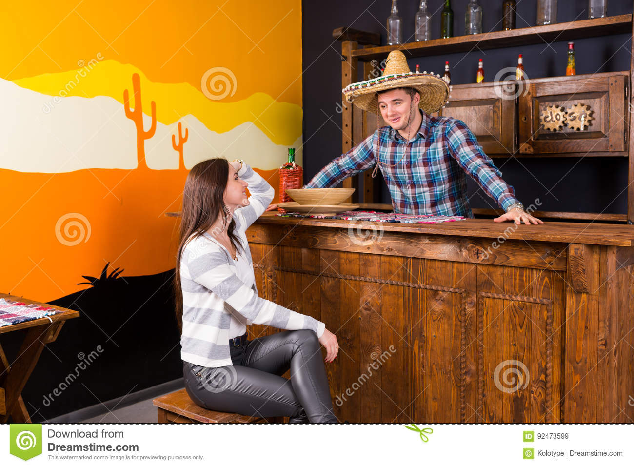 A Young Woman Sitting At The Bar Counter Next To The Bartender W