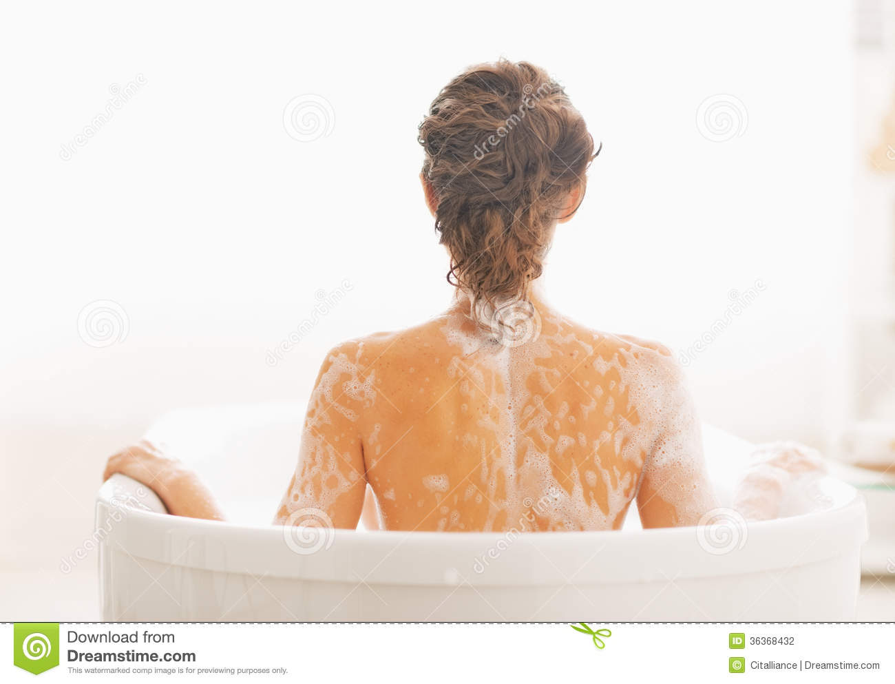 Stock Photography of Young naked woman sitting in bathtub