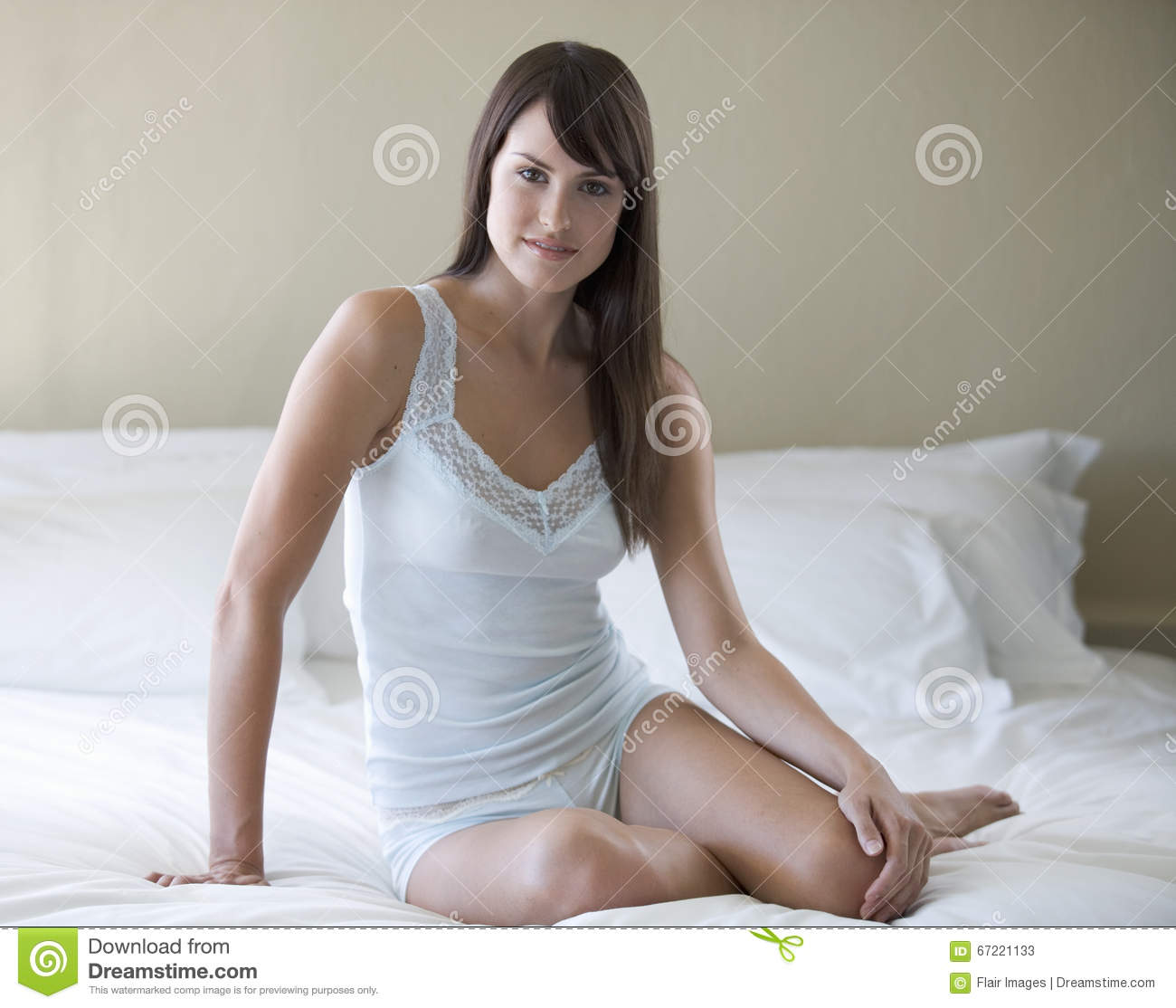 A young woman sitting on a bed