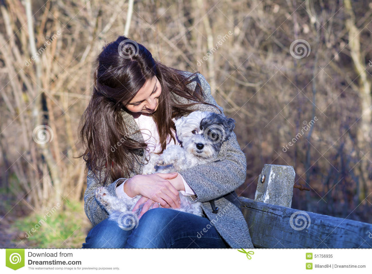 Young woman sitting on a bench hugging her dog