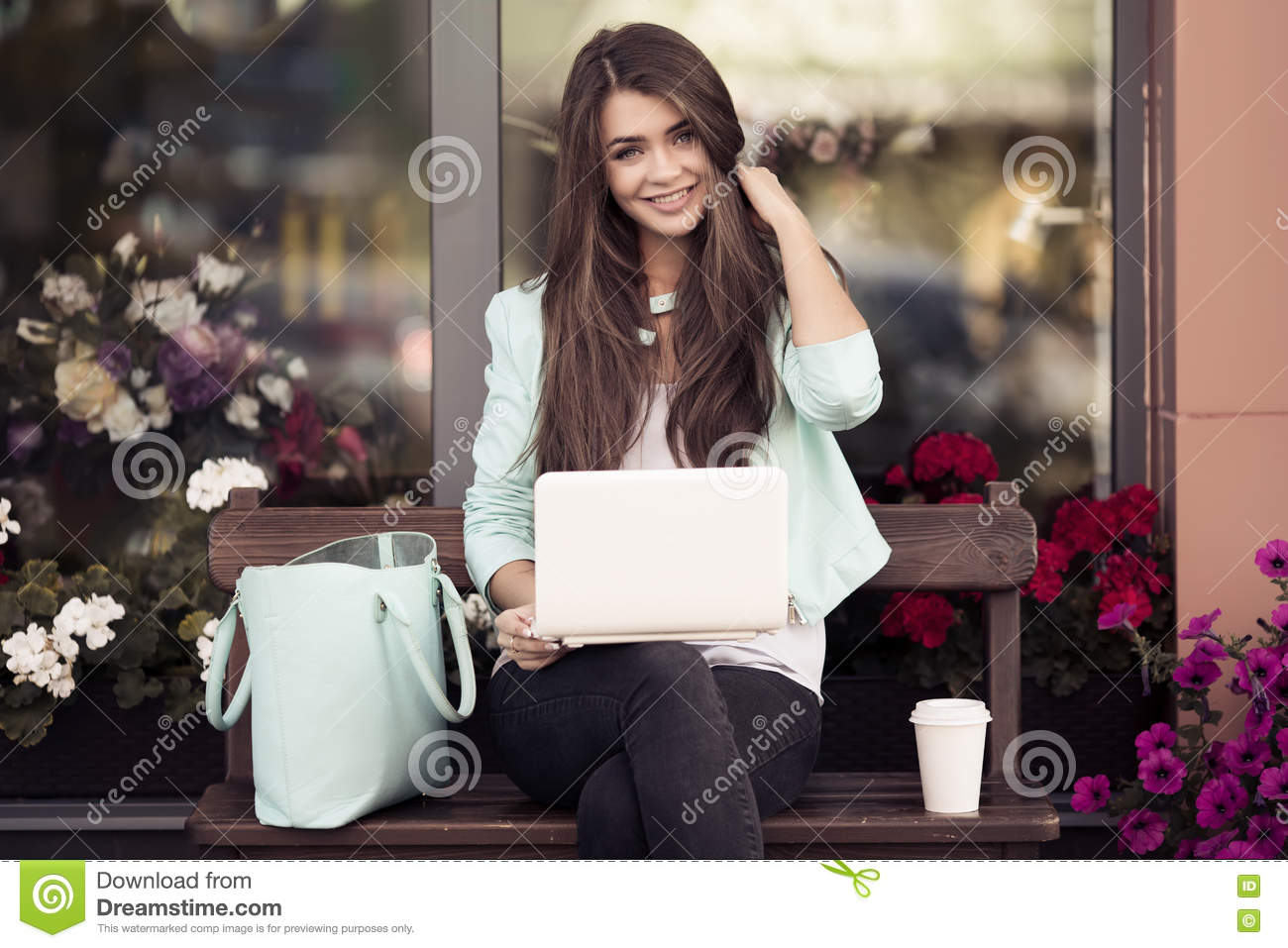 Young Woman Sitting On The Bench And Using Laptop