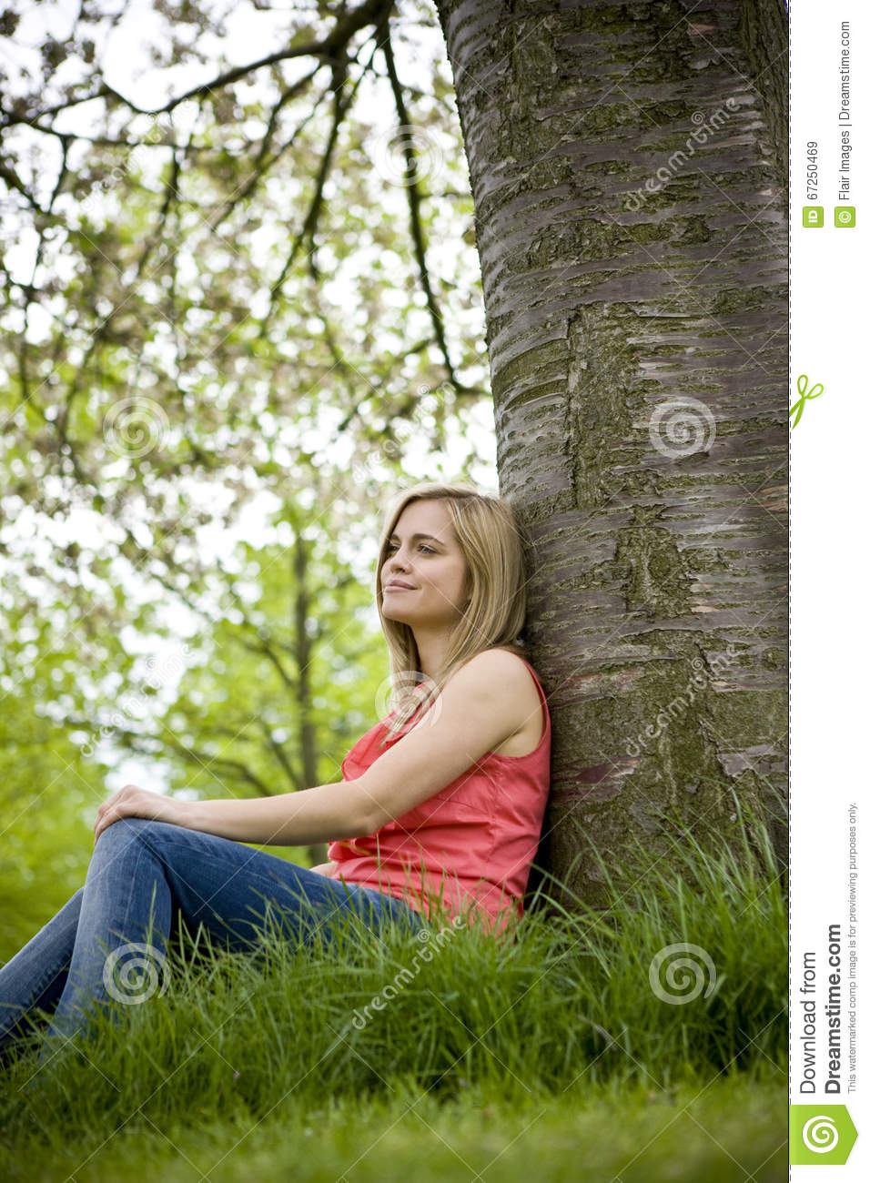 A young woman sitting beneath a tree, looking thoughtful