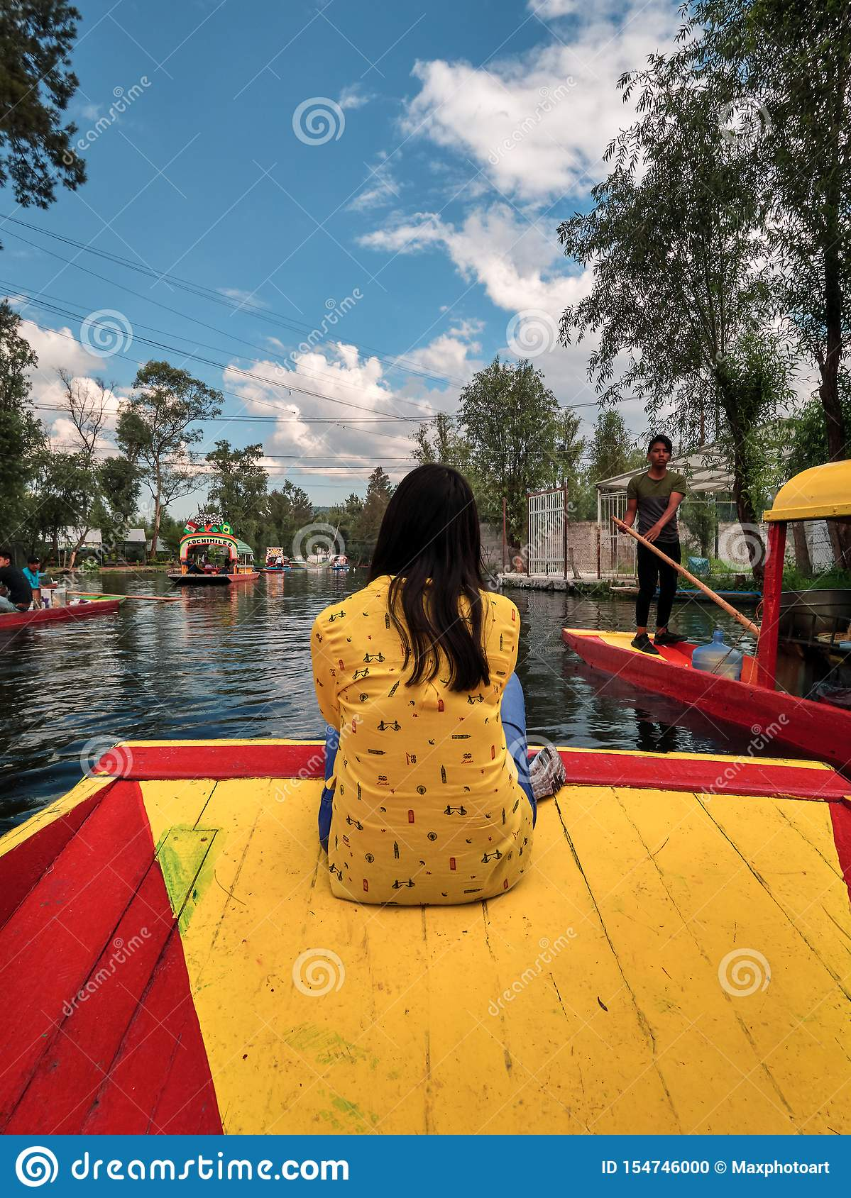 Young woman sitting on bow of traditional Xochimilco boat