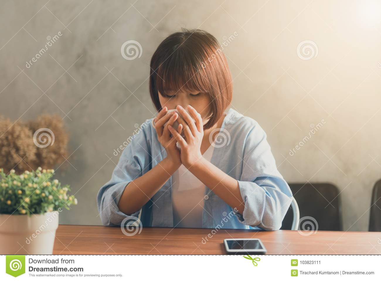 Young woman sitting in coffee shop at wooden table, drinking coffee and using smartphone.