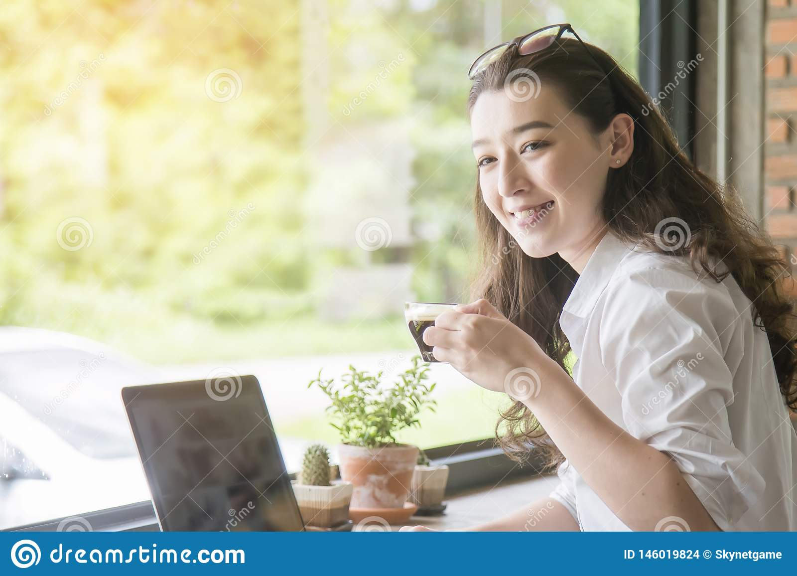 Young woman sitting in coffee shop at wooden table, drinking coffee and using smartphone.On table is laptop for internet shopping