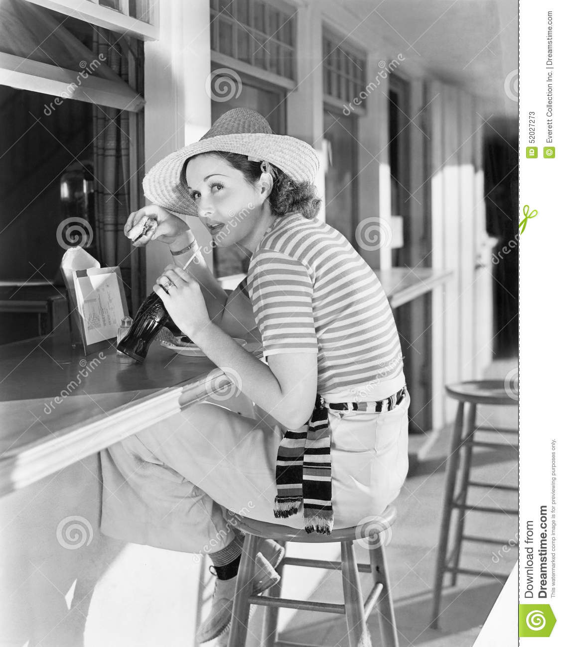 Young woman sitting at a counter drinking a coca cola