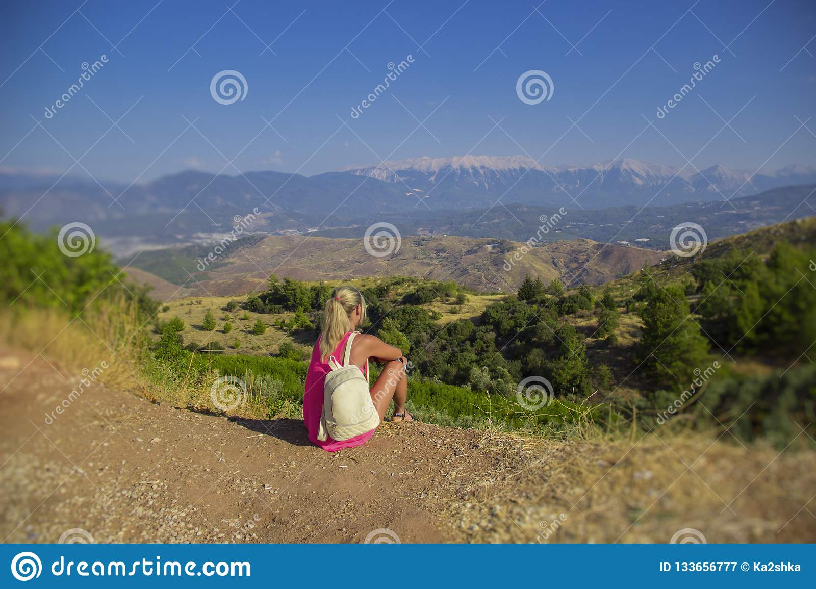 Young woman sitting at edge of cliff looking over expansive view of plains and mountains