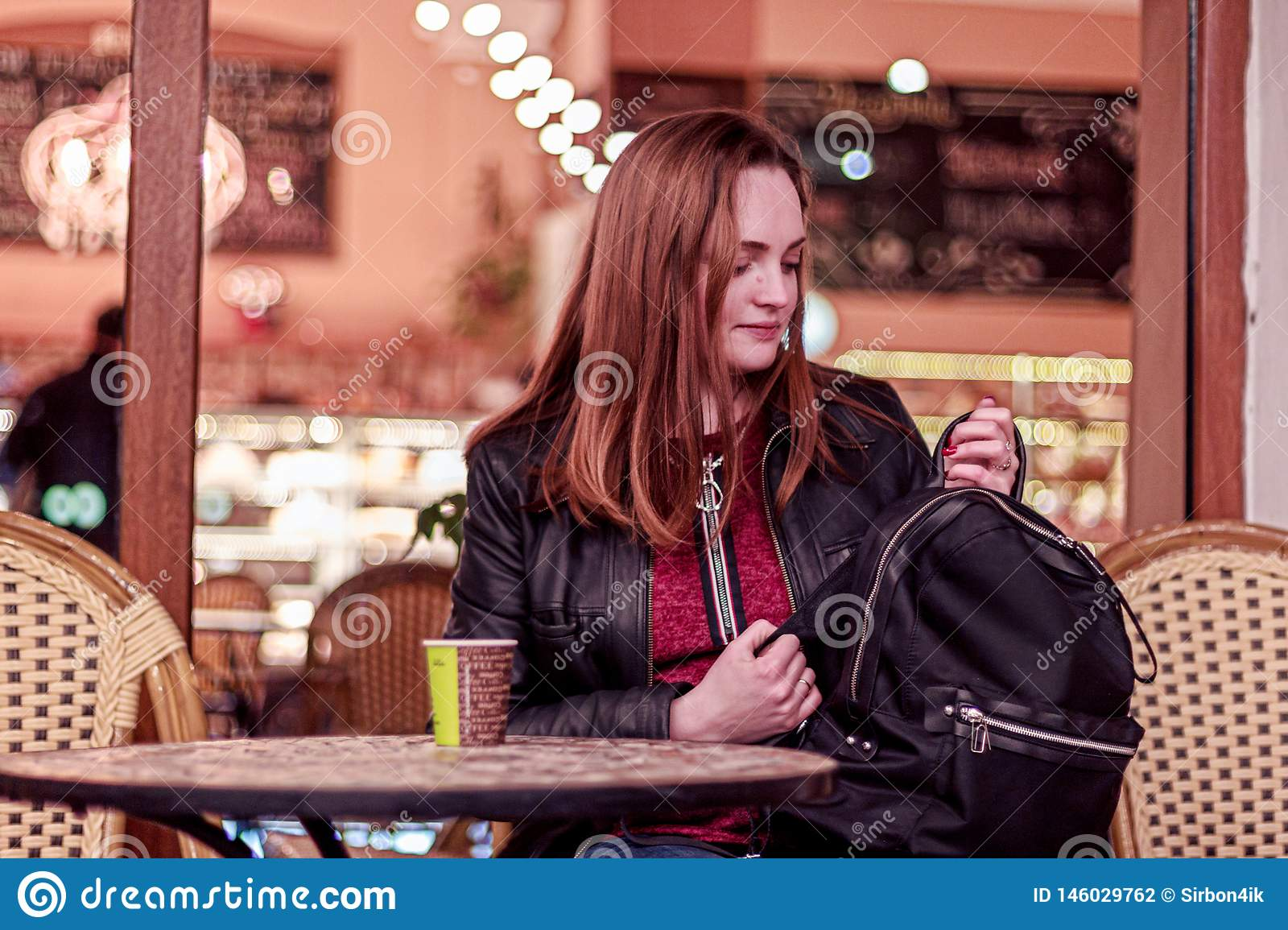 Young woman sitting in the evening in a cafe and looking to black backpack