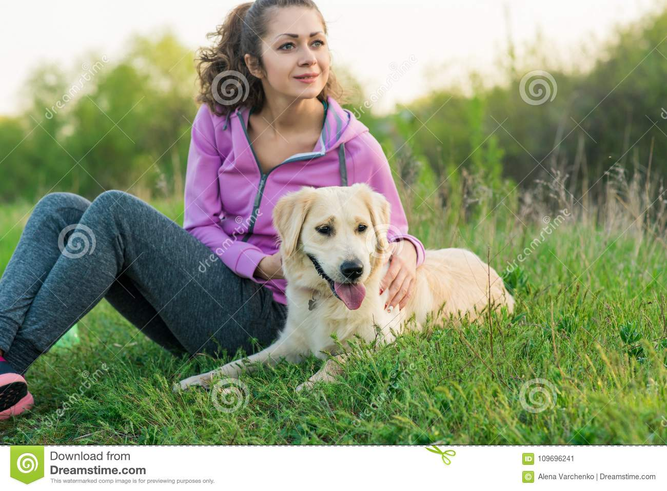 Young pretty girl running outdoor in the spring with dog