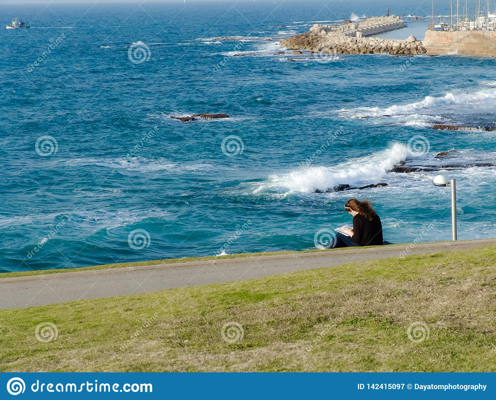 Young woman sitting on green grass at the park, reading, overseeing a view of the ocean and Jaffa harbor