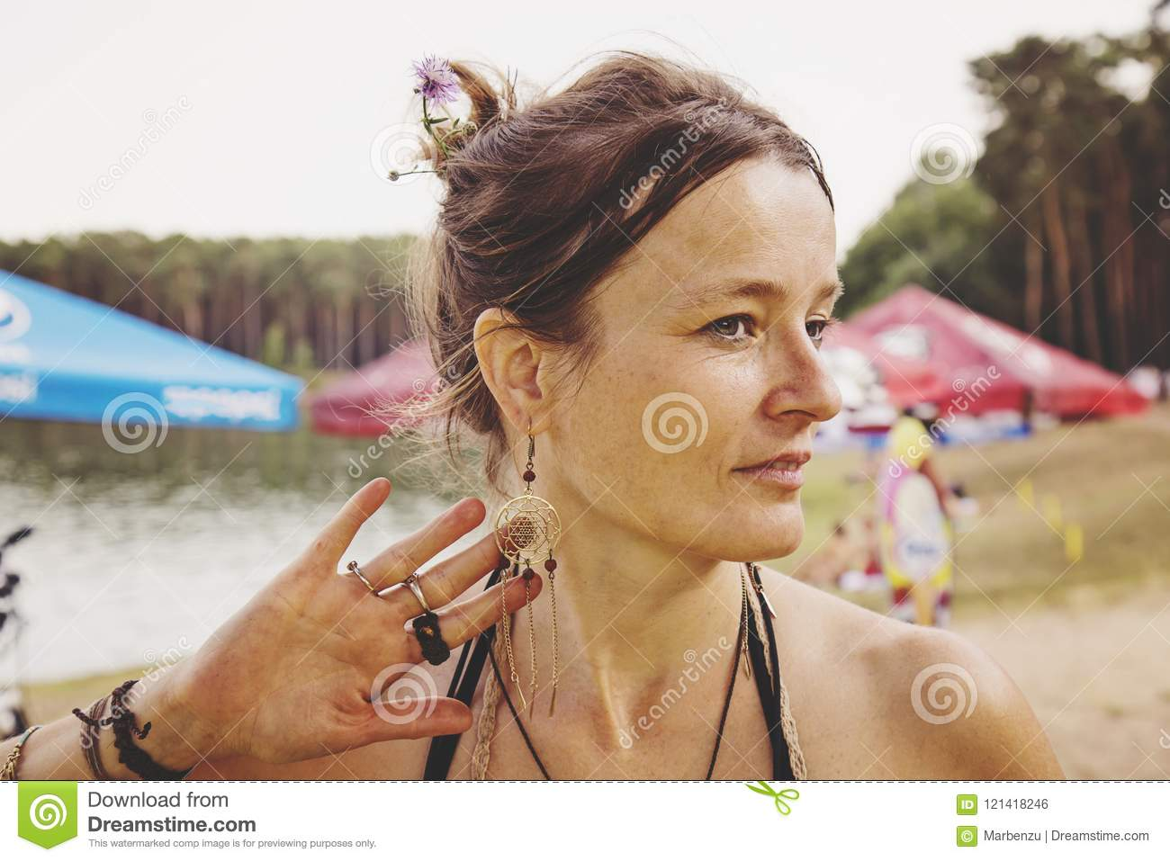 Young woman sitting by a lake and playing with her earring