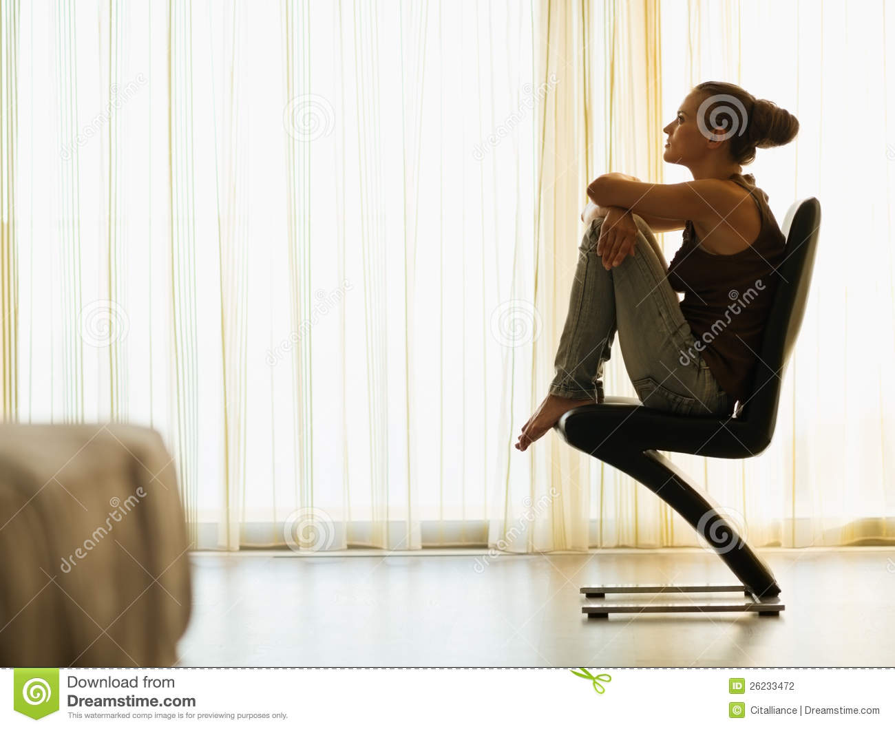 Young woman sitting on modern chair near window stock for Modern sitting chairs