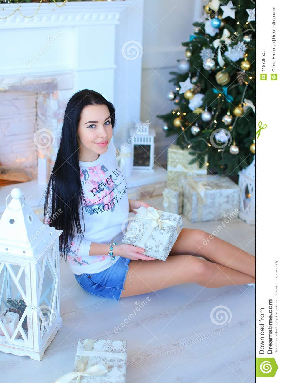 Young woman sitting near Christmass tree and keeping present.
