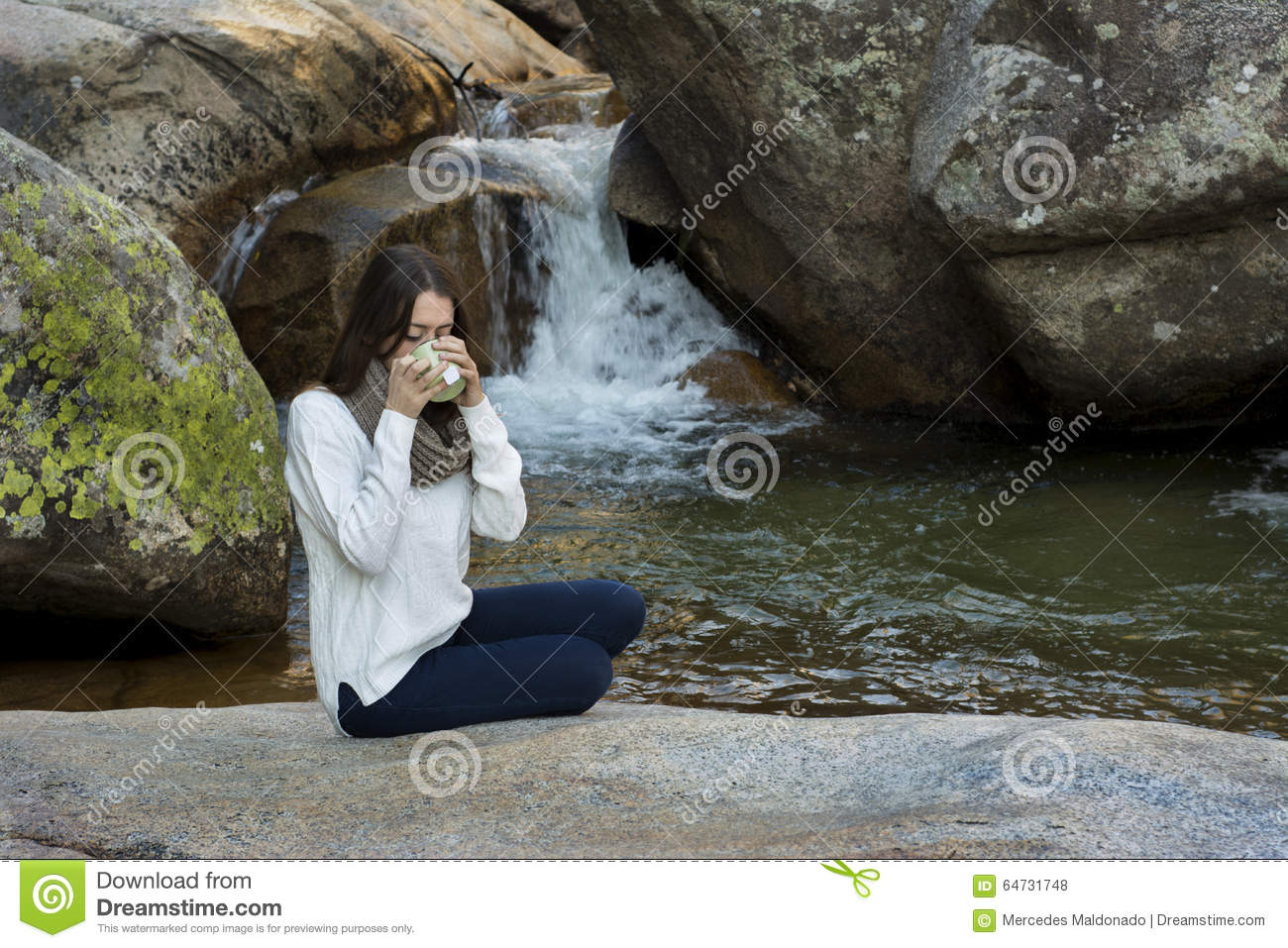Young woman sitting near the waterfall and drinking tea, surrounded by large rocks