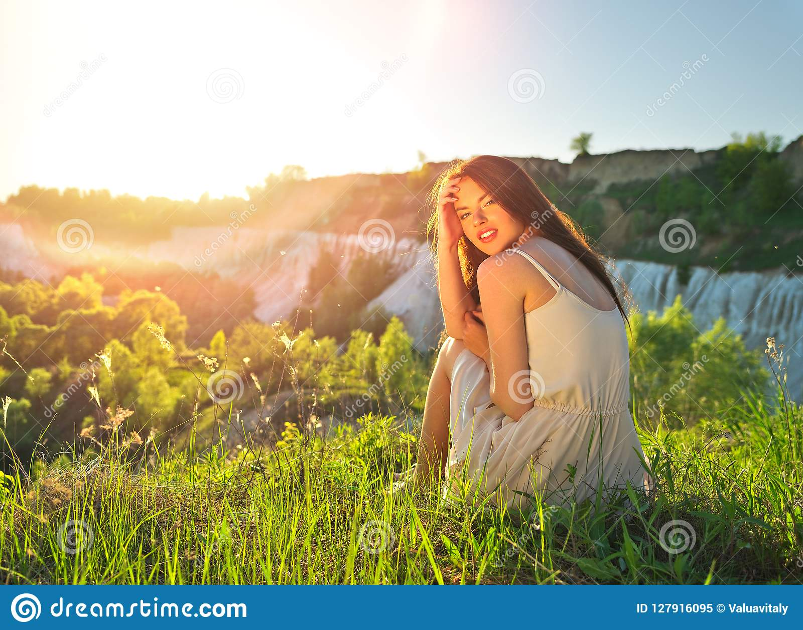 Young Woman Sitting Outdoors On Nature Durring Sunset