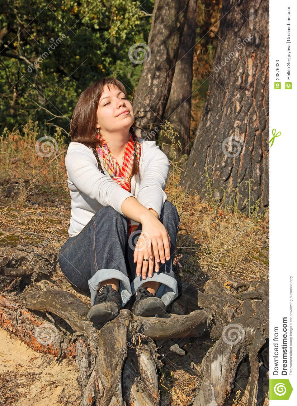 Young woman sitting on root
