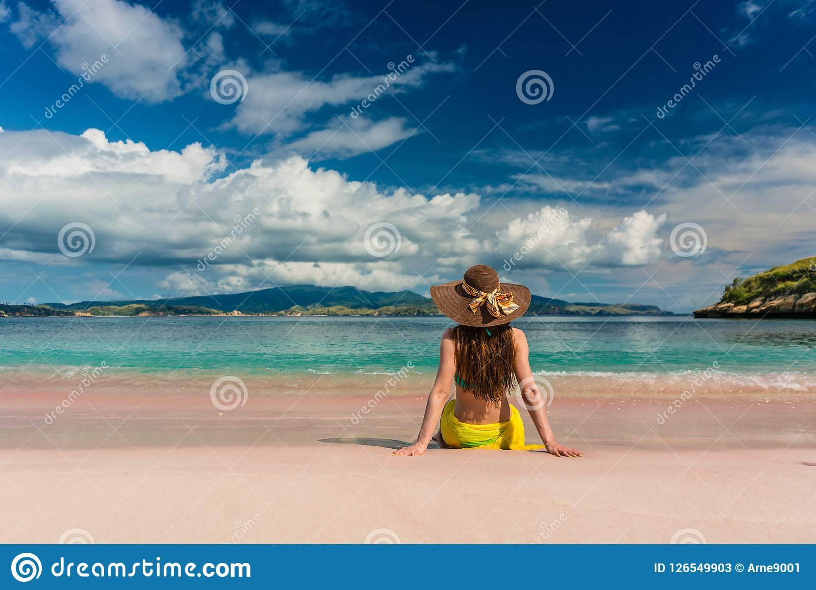 Young woman sitting on the sand at Pink Beach in Komodo Island