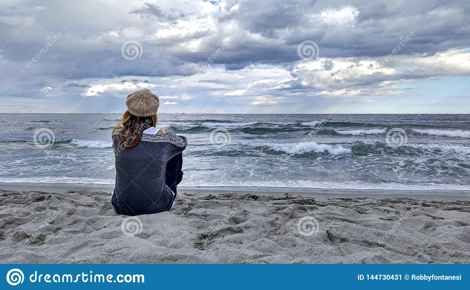 Young woman sitting by the sea with stormy sky, looks at the horizon thoughtfully