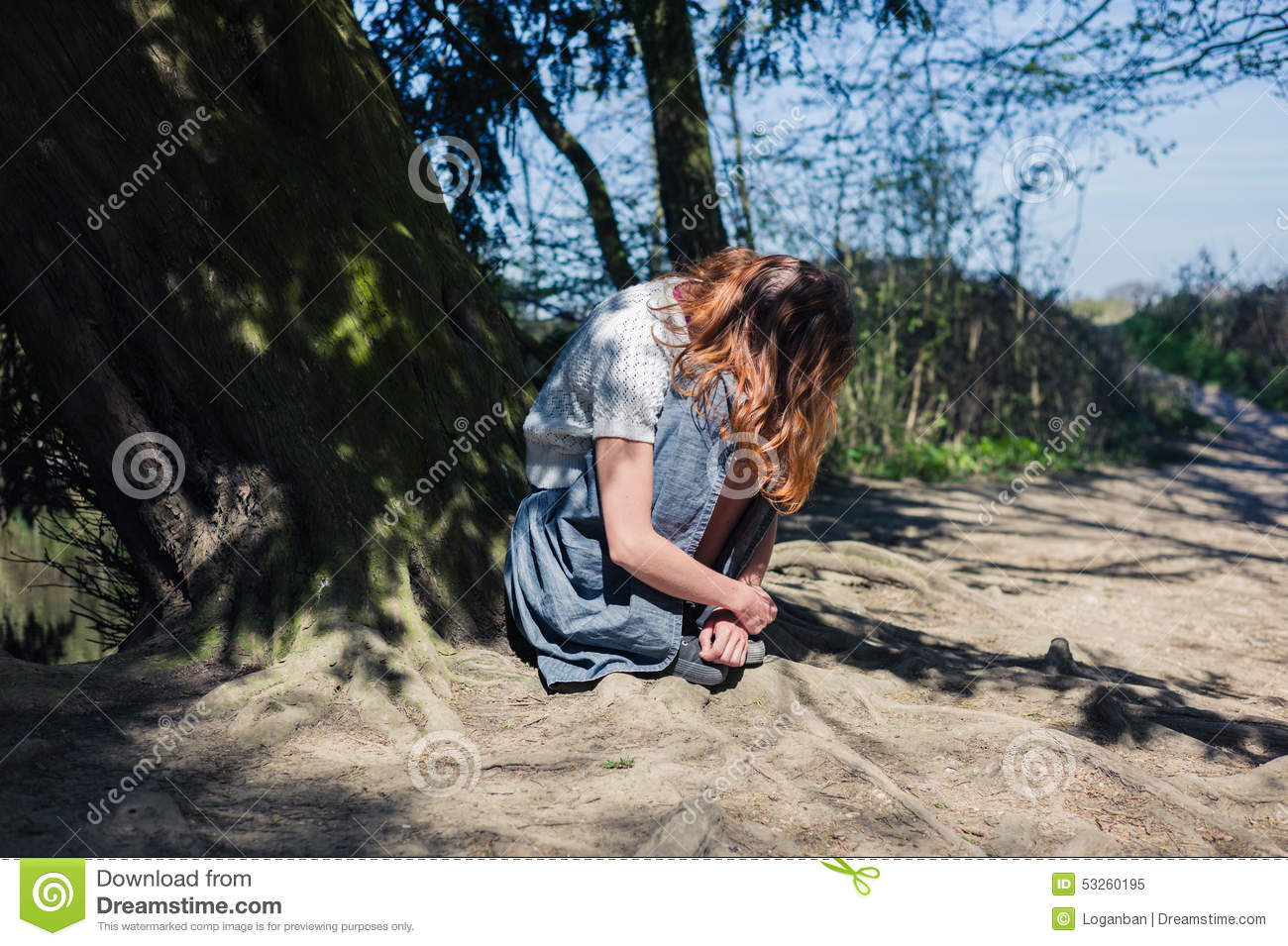 Young woman sitting under tree by the water