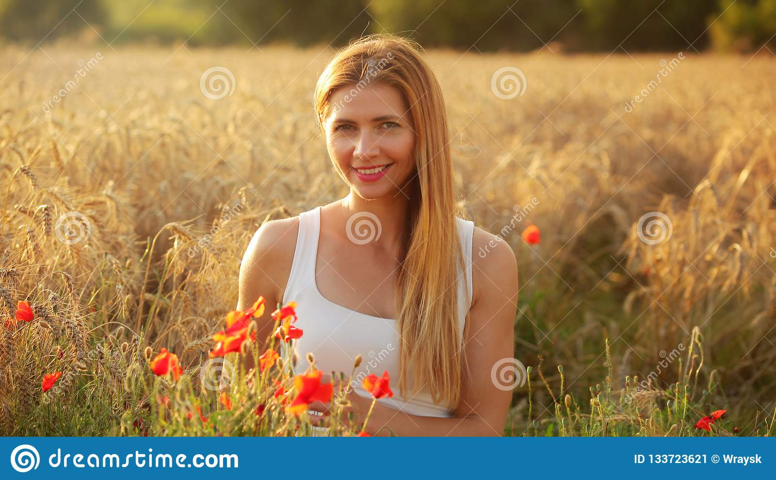 Young woman sitting in wheat field, lit by afternoon sun, few re