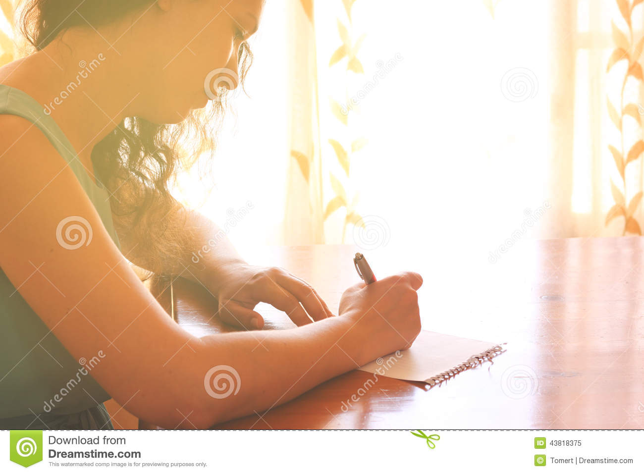 Young Woman Sitting And Writing Letter Near Bright Window