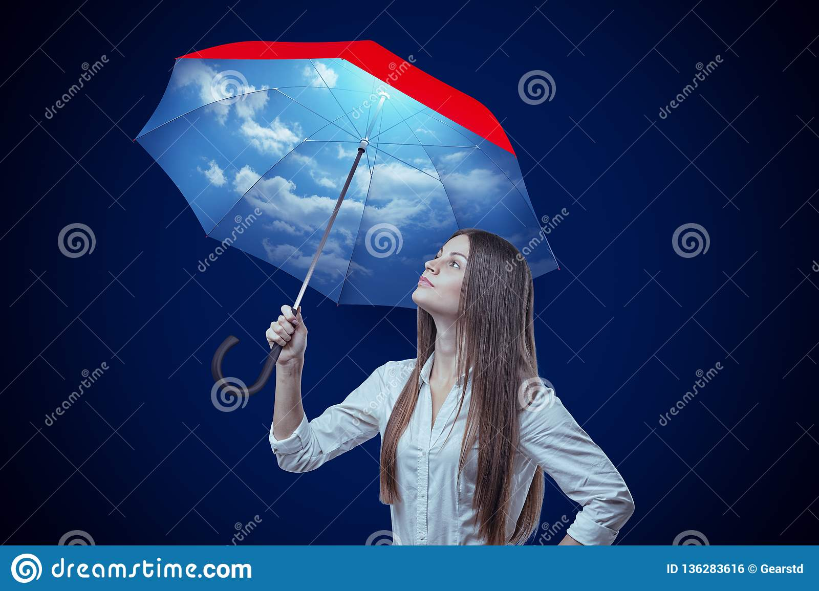 Young woman with sky design umbrella on dark blue background