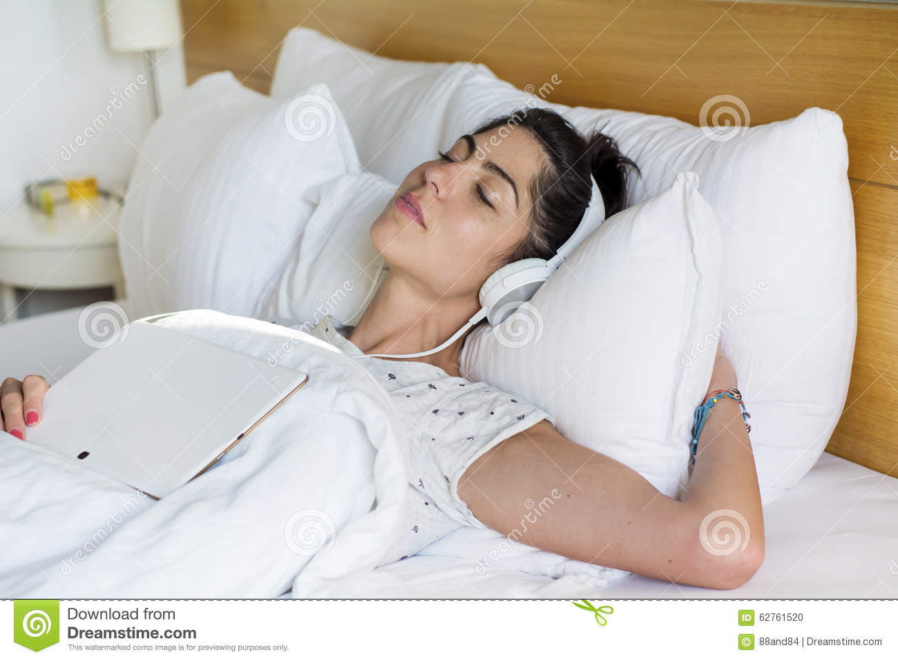 Young woman sleeping in bed listening music
