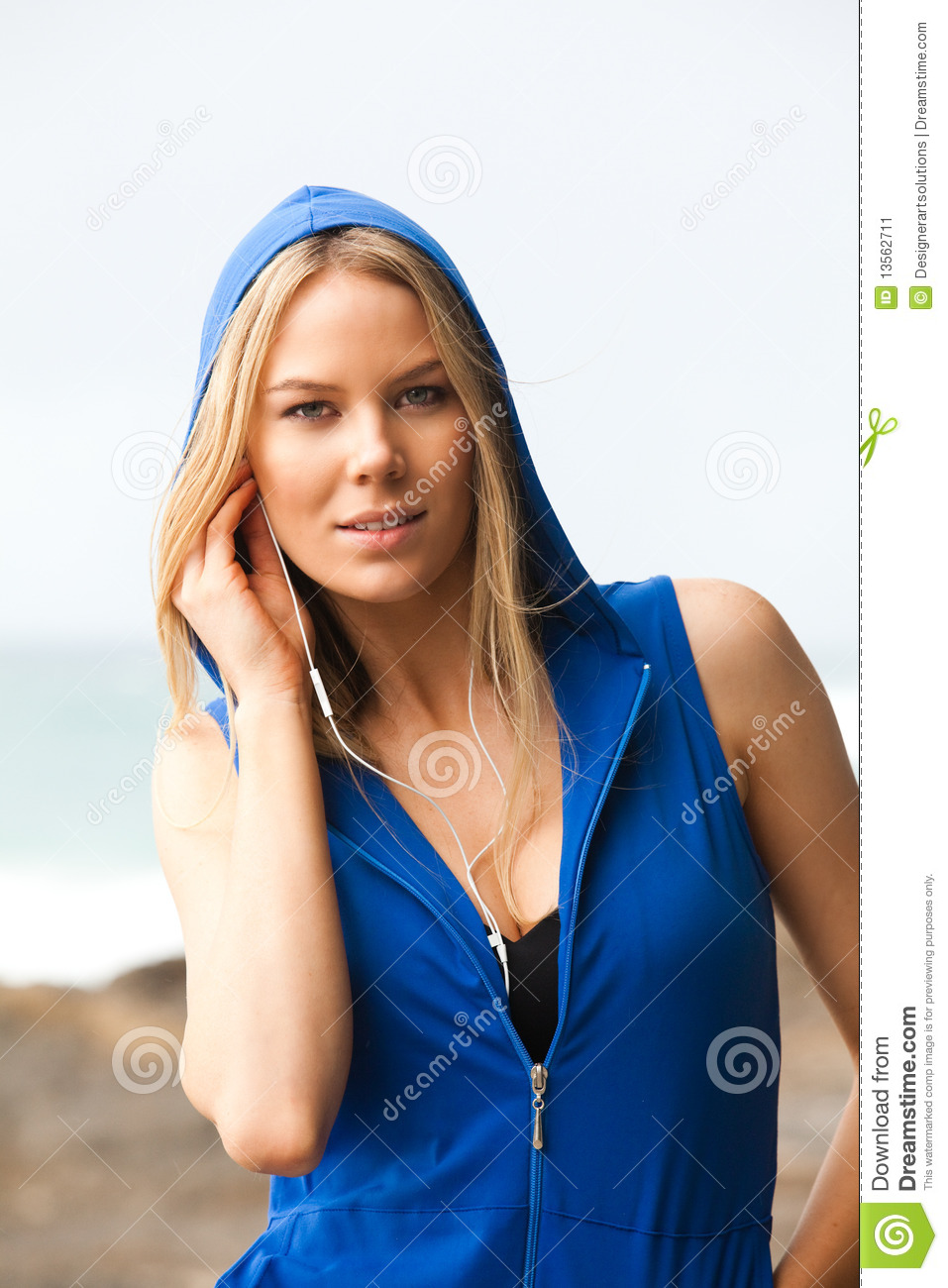 Portrait of a young woman wearing a sleeveless hoodie and headphones