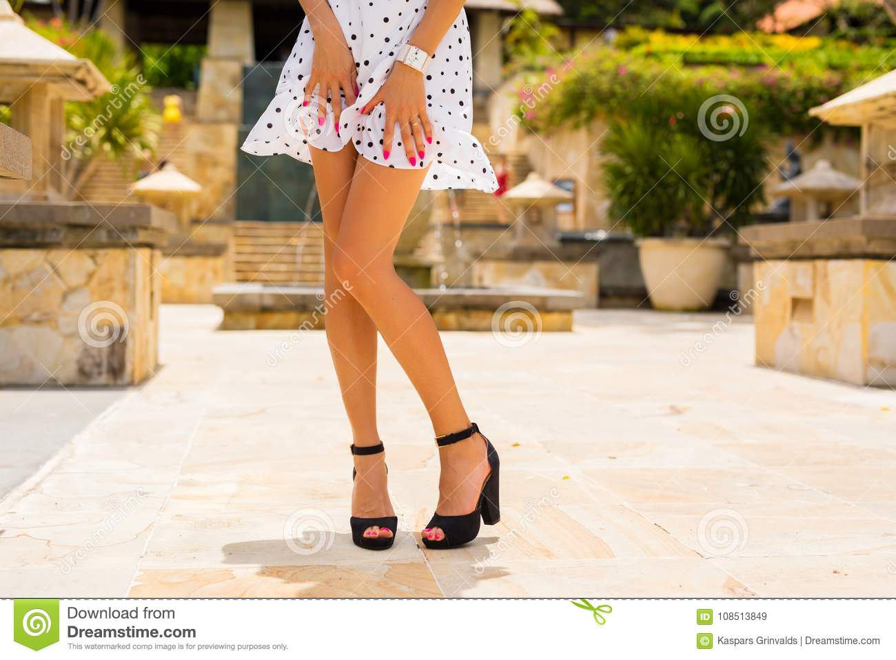 Woman With Slim Legs Posing In White Summer Dress And Black High Heels