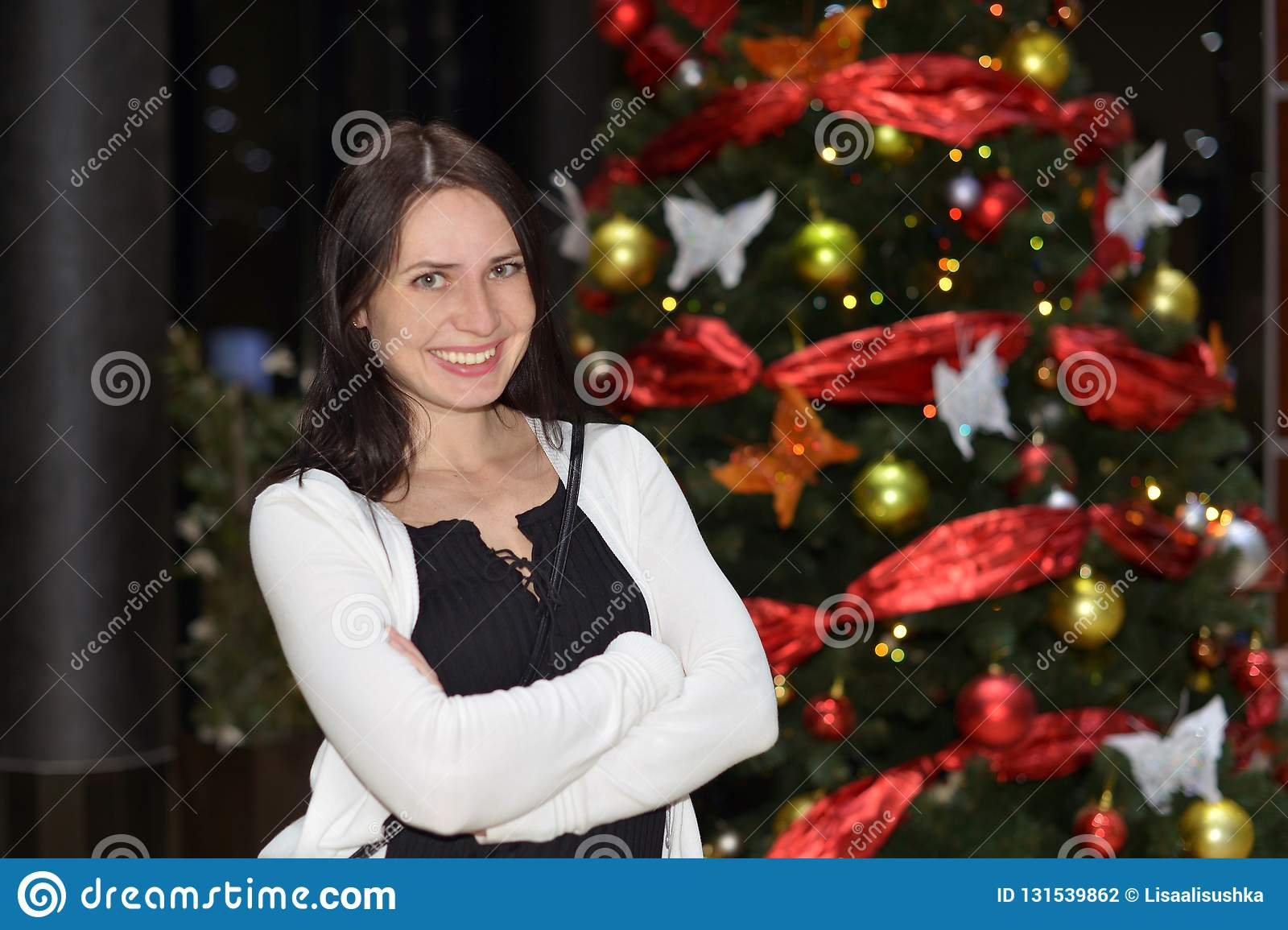 A young woman smiling stands near the Christmas tree.