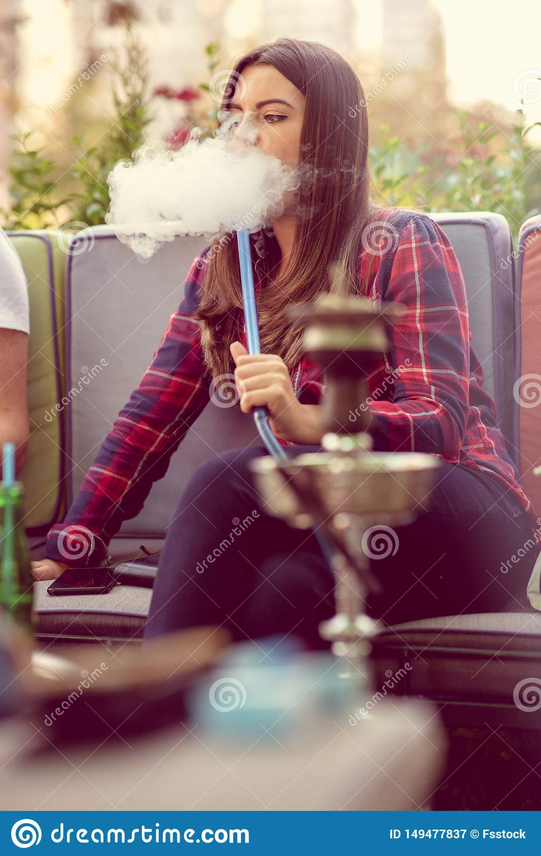 Young woman smoking a hookah outdoors. The pleasure of smoking. City in background