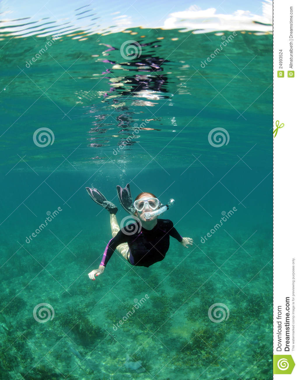 Pretty young woman snorkeling underwater in clear blue ocean