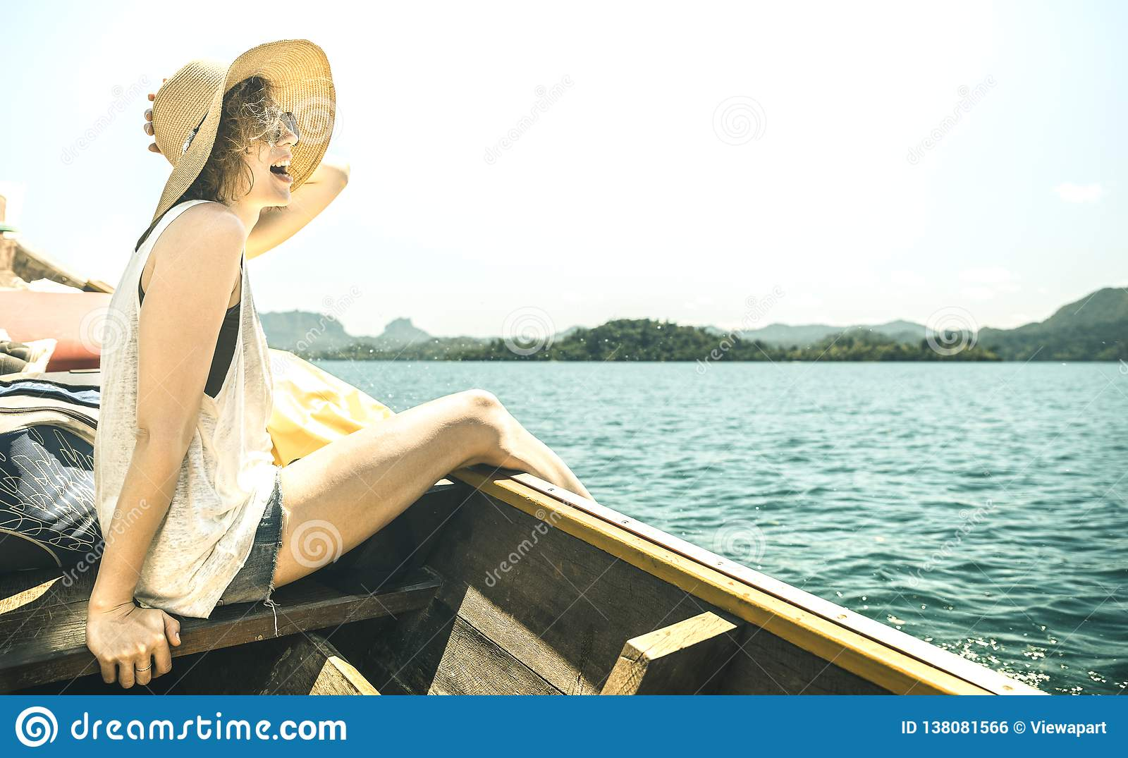 Young woman solo traveler at boat trip excursion at lake - Wanderlust travel concept with adventure girl tourist wanderer on