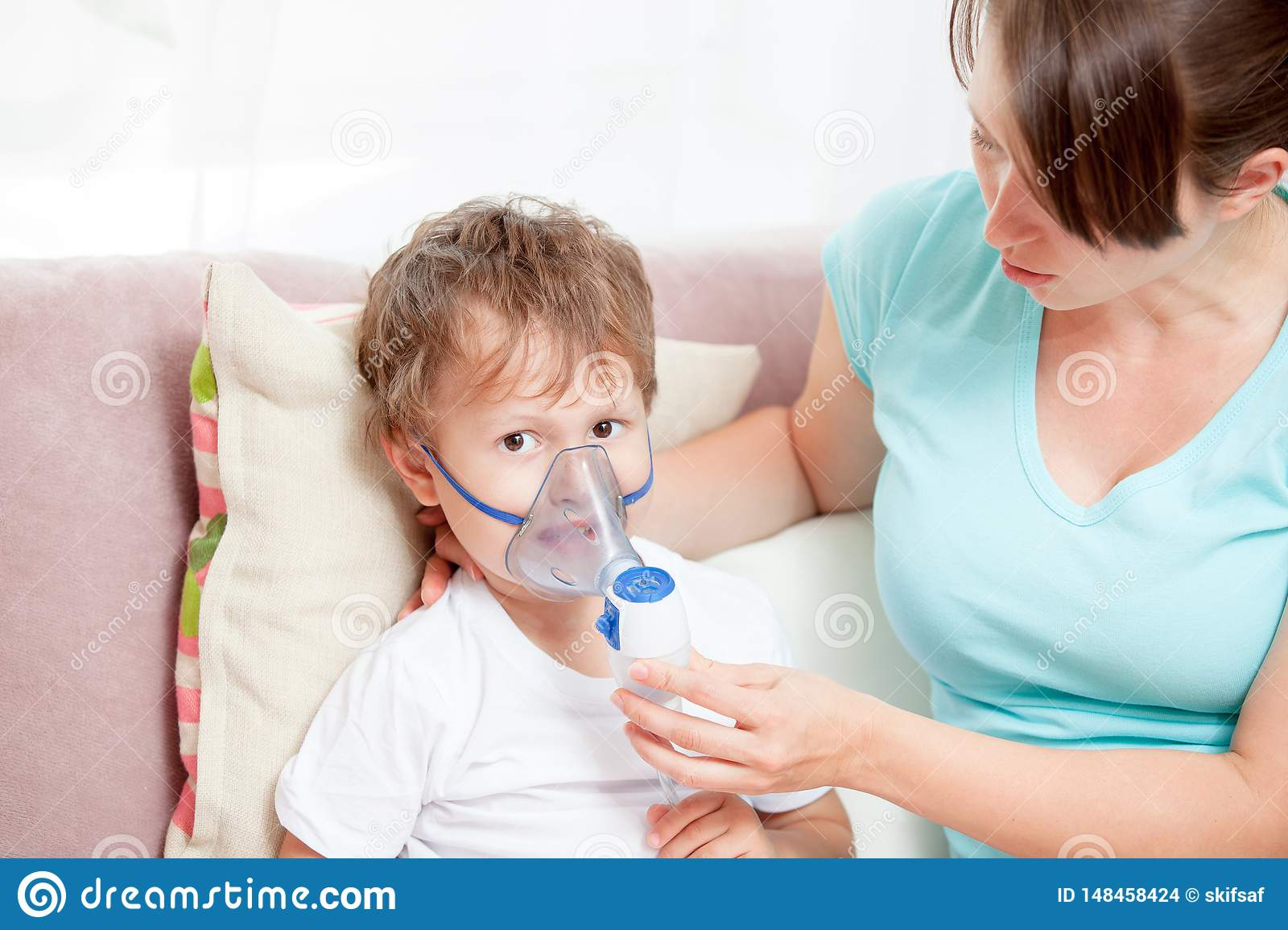 Young woman with son doing inhalation with a nebulizer at home