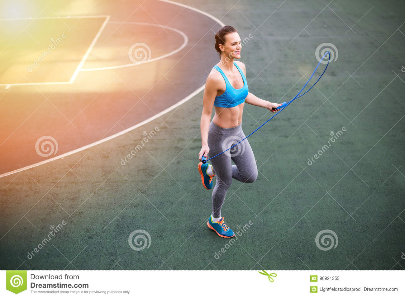 Young woman in sportswear exercising with skipping rope on stadium