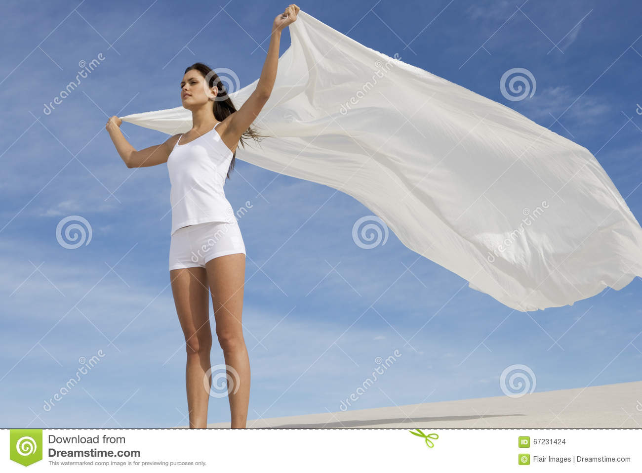 A young woman standing in the desert with a sheet