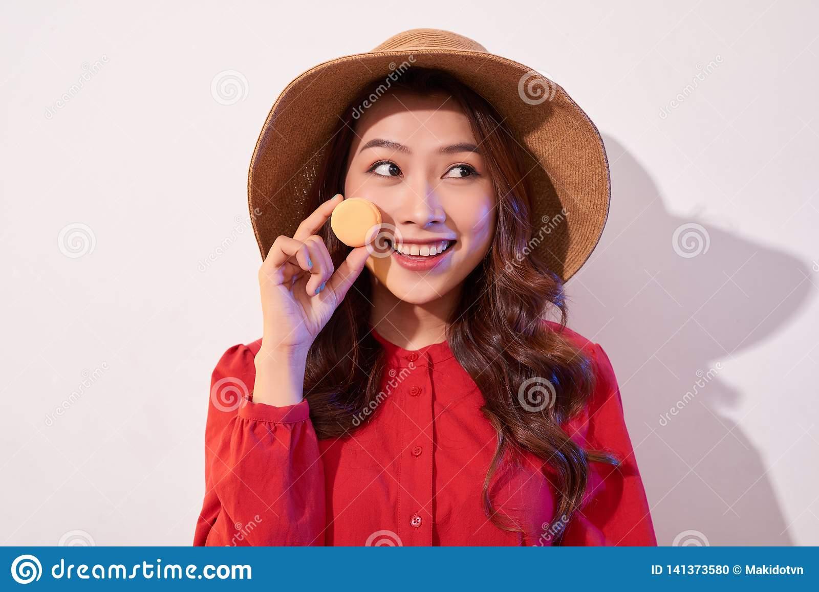 Young woman standing with french sweet cookie macaron over white background
