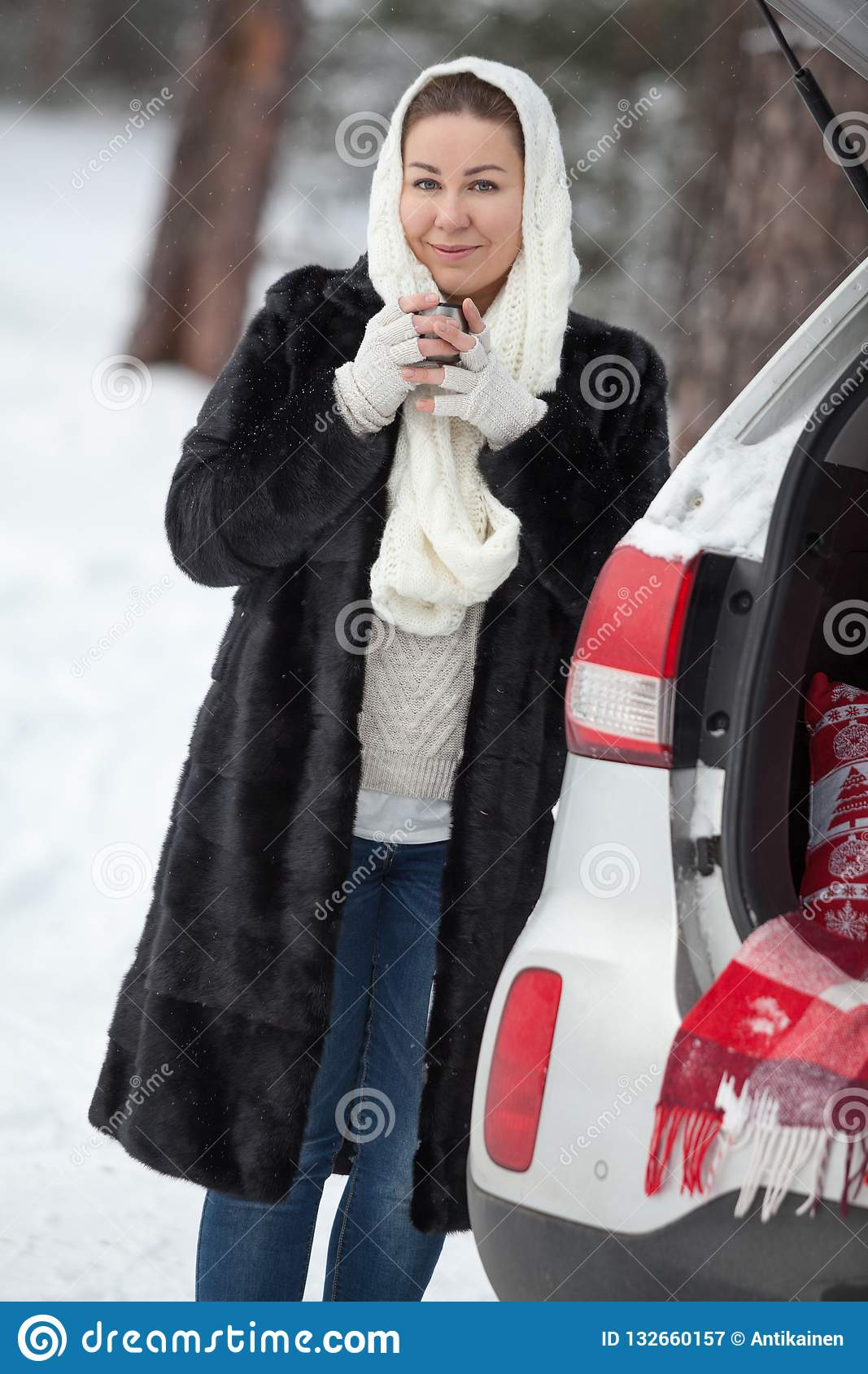 Young woman standing near suv and holding tea mug in hands at winter season