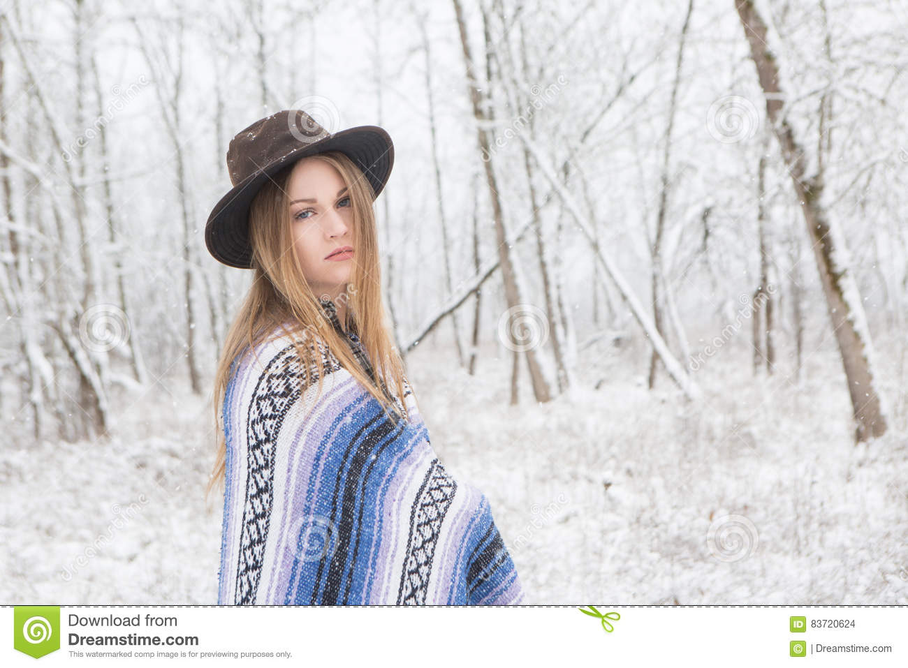 Young Woman Standing In Snow With Bohemian Style Hat And Blanket. Stock Photo